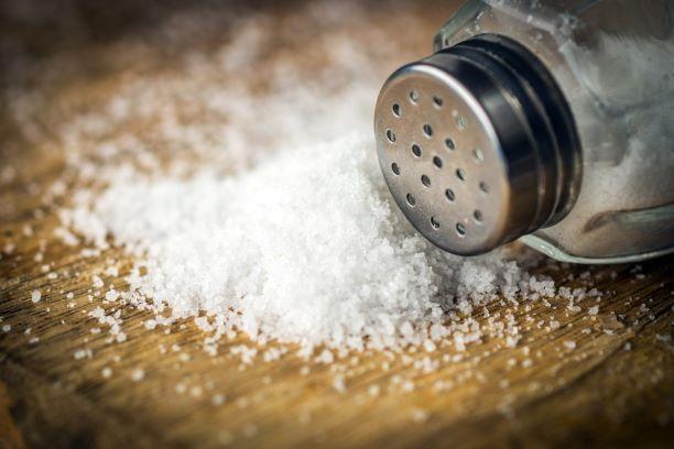 Salt Shaker and Salt on cutting board.
