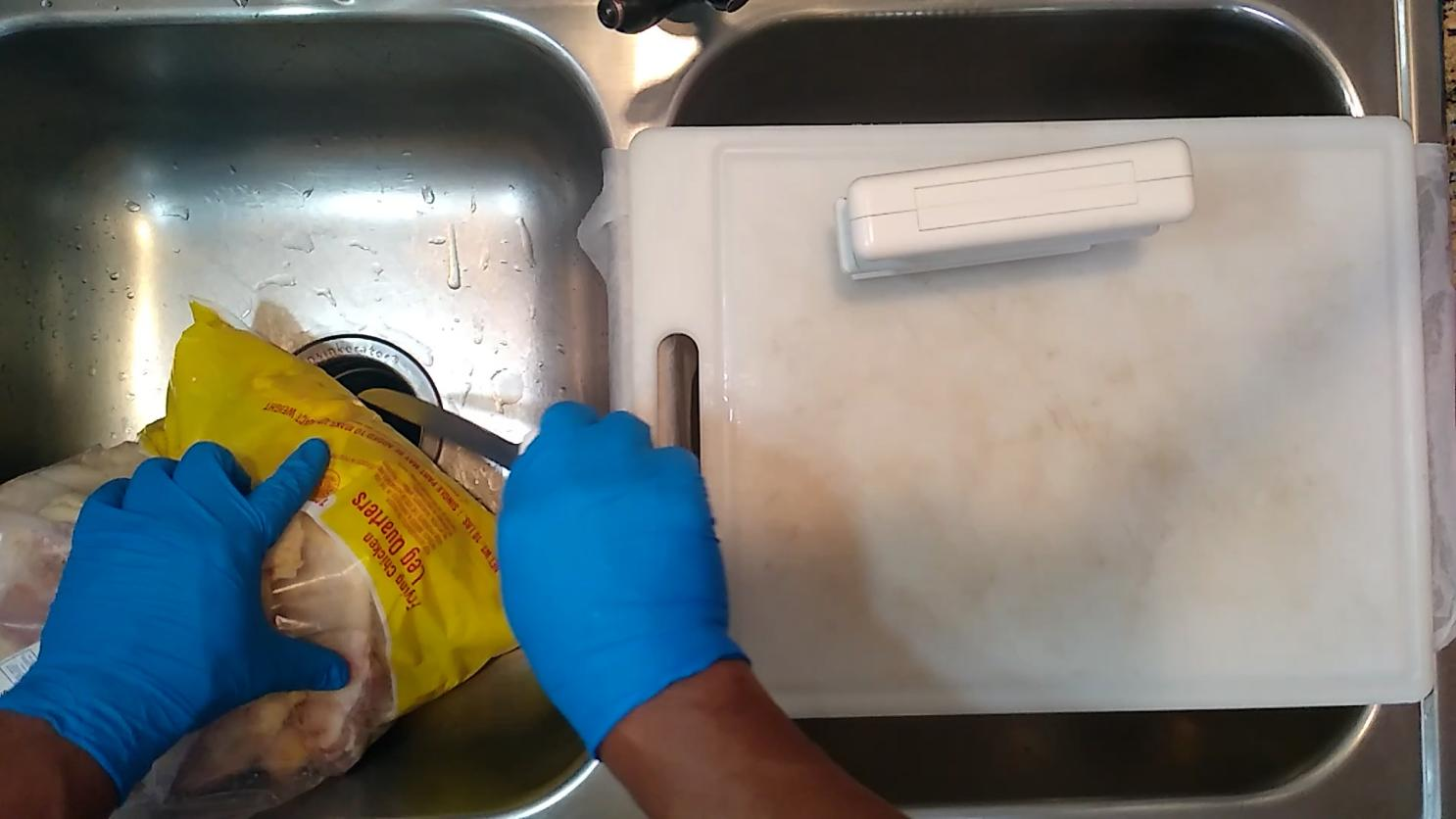 10lb bag of chicken quarters cutting the bottom to drain blood and bits